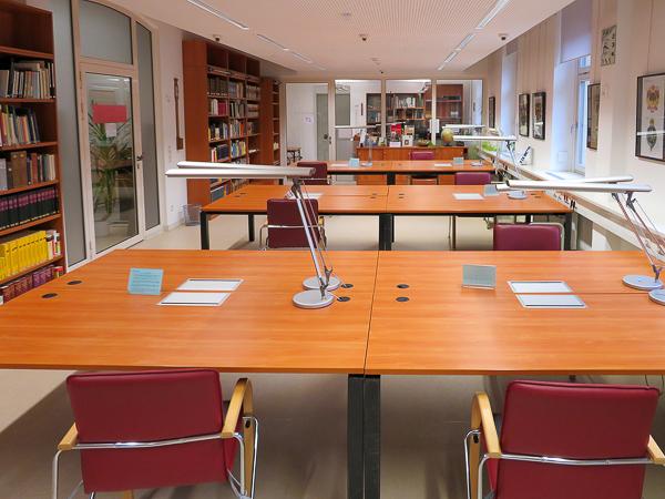 Blick in den Lesesaal mit Arbeitstischen und Bücherregalen