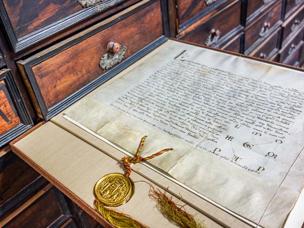 Mittelalterliche Urkunde vor einem Archivschrank aus Holz