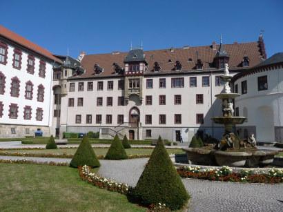 Großes Gebäude mit weißer Fassade und rotgerahmten Fenstern mit einem Springbrunnen und Rasen im Vordergrund