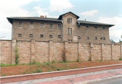 Von übermannshoher Steinmauer umgebenes mehrstöckiges Gebäude mit grauer Fassade