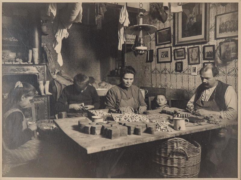 Eine Heimarbeiterfamilie sitzt in der Wohnstube am Tisch und fertigt Spielsachen aus Einzelteilen