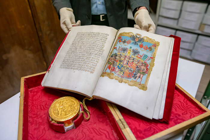 Aufgeschlagenes Adelsdiplom mit Wappenbild und goldenem Siegel