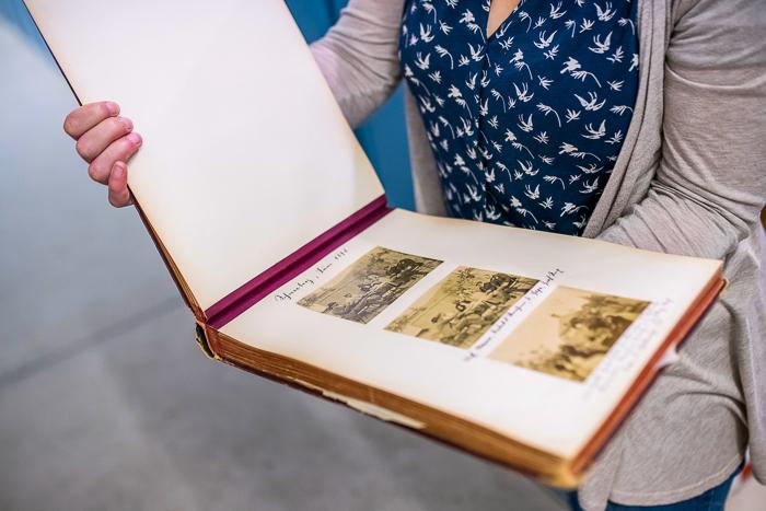 Eine Archivmitarbeiterin hält ein geöffnetes Fotoalbum in die Kamera.