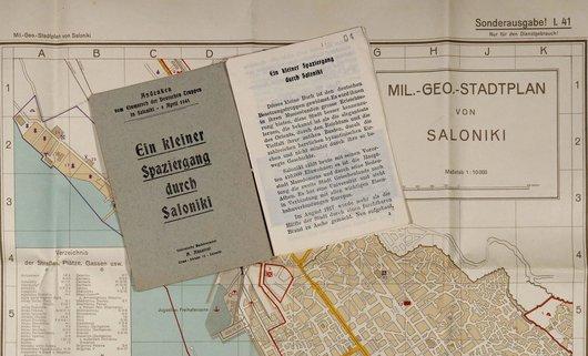 alter Stadtplan von Saloniki in Griechenland und obenauf ein aufgeschlagenes Buch liegend