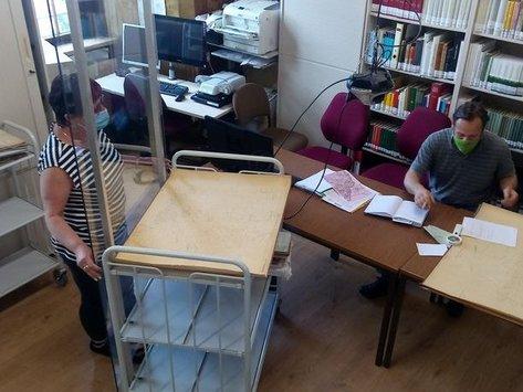 Mitarbeiterin des Archivs im Lesesaal hinter einer an einem Rollwagen befestigten Schutzscheibe