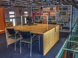 Arbeitstisch mit Computer und Bücherregalen im Hintergrund