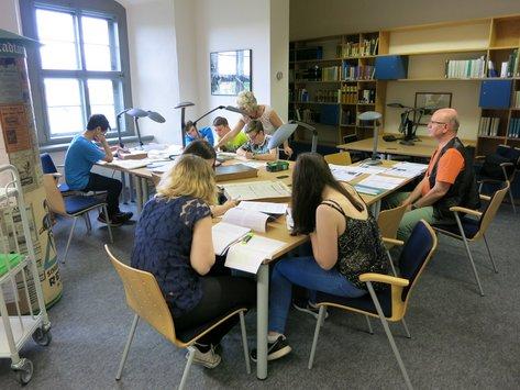 Schüler mit Lehrer und Archivarin im Lesesaal