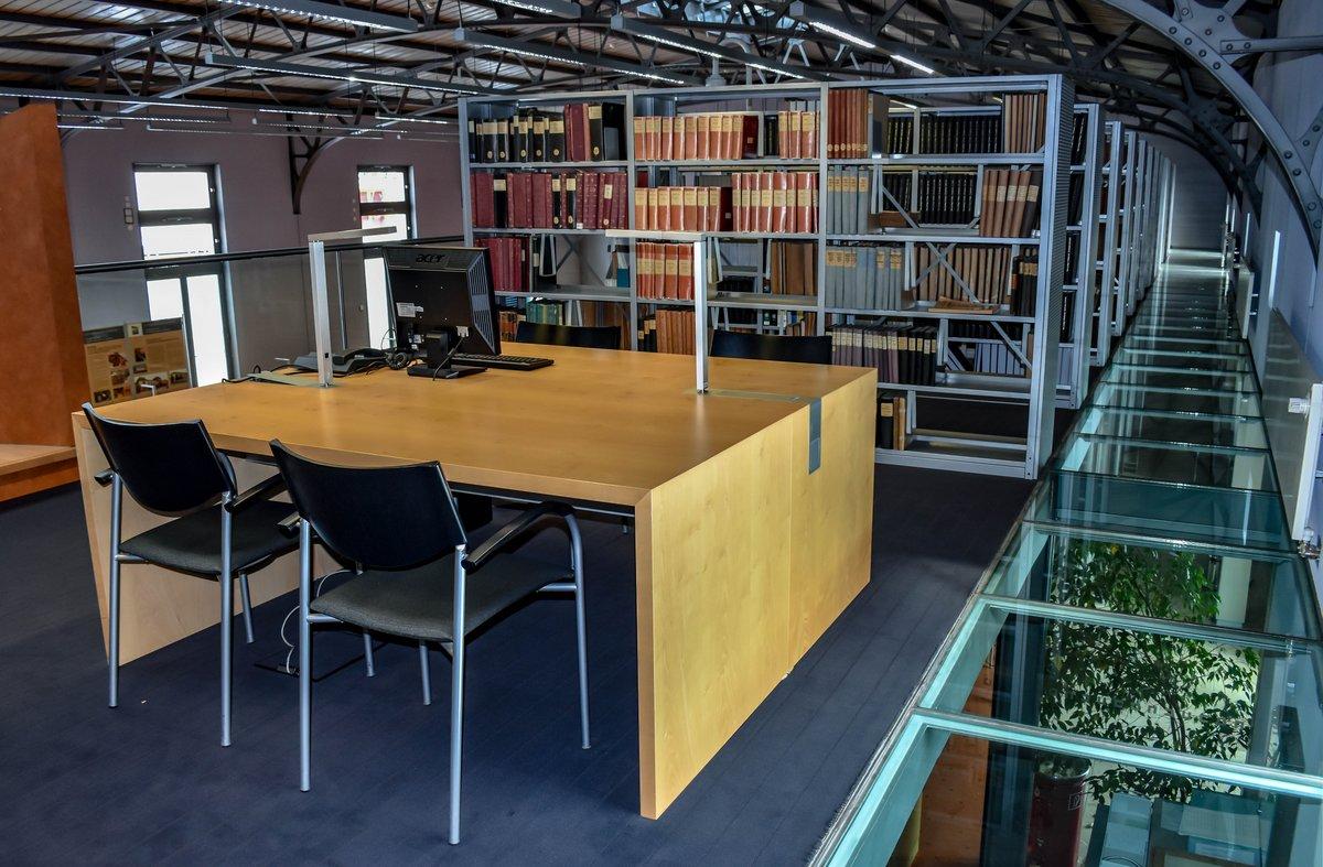 Ein Arbeitstisch mit Stühlen vor Bücherregalen auf der Empore des Lesesaals mit der sichtbaren Stahlkonstruktion der ehemaligen Reithalle.